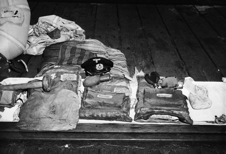 All that has come in from the Nazi Sub U-853, which torpedoed a collier off Pont Judith, R.I., shortly before the German Capitulation, is this assortment of wreckage and clothing. Included above are the captain's cap, artificial lungs, a mattress and pillow, a liferaft, a towel, and what appears to have been part of her flagstaff. The sub was destroyed by depth charges dropped in shallow water by the USS Atherton, a destroyer escort shown May 16, 1945.