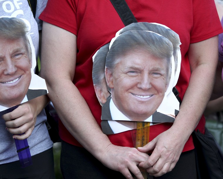 Image: A woman holds signs depicting the head of Republican presidential candidate businessman Donald Trump