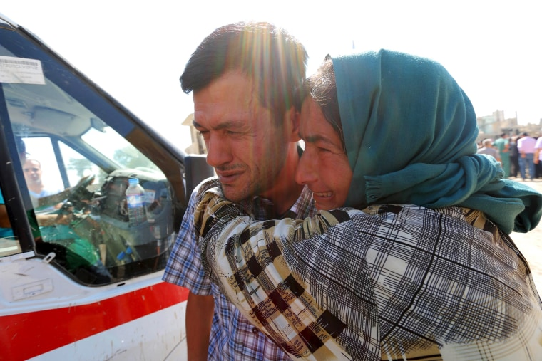 Image: Abdullah Kurdi mourns with his relative during the funeral of his toddlers at the Syrian border town of Kobani