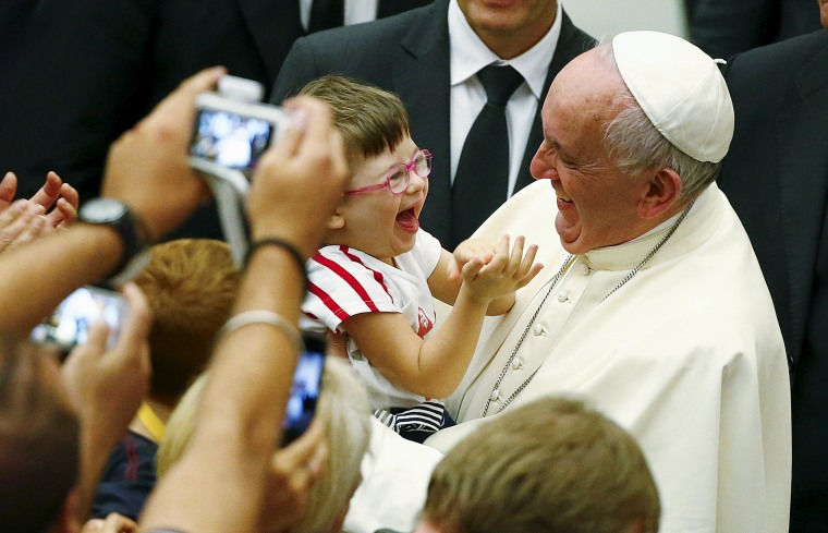 Image: Pope Francis laughs with a baby during a special audience with parish cells for the evangelization in Paul VI hall at the Vatican