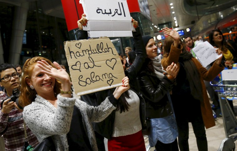 Image: Wellwishers applaud and hold up signs welcoming migrants as Syrian families disembark a train that departed from Budapest's Keleti station at the railway station of the airport in Frankfurt