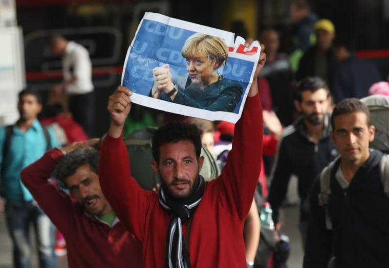 Image: A migrant arriving in Germany holds a picture of Angela Merkel