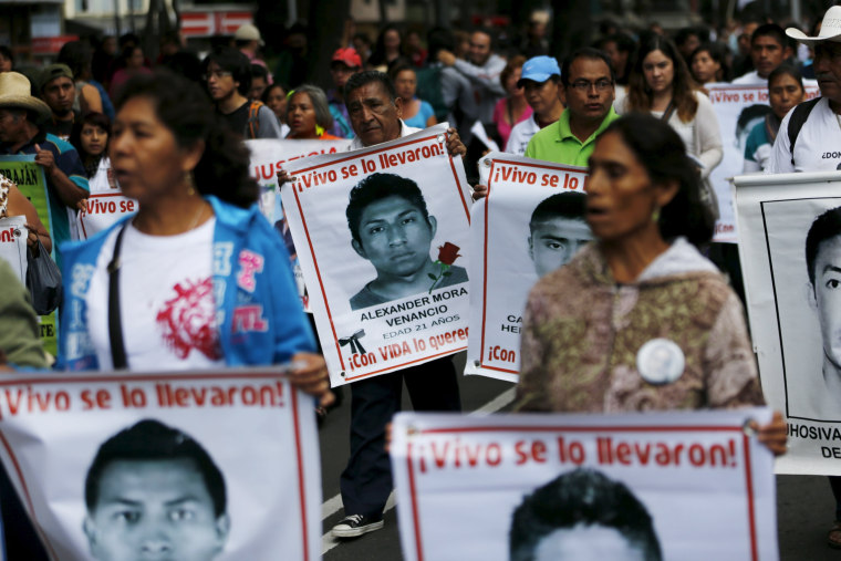Image: Relatives carry photos of some of the 43 missing students of the Ayotzinapa teachers' training college during a protest to mark the eleven-month anniversary of their disappearance in Mexico City