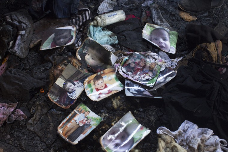 Image: Pictures sit on the floor of a West Bank home that was destroyed by a fire suspected to have been set by Jewish extremists