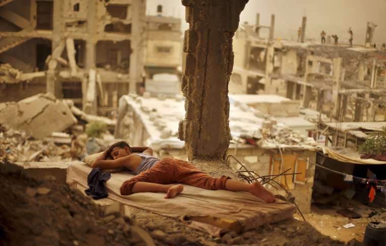 Image: Palestinian boy sleeps on a mattress inside the remains of his family's house that witnesses said was destroyed by Israeli shelling during a 50-day war in 2014 summer during a sandstorm in Gaza
