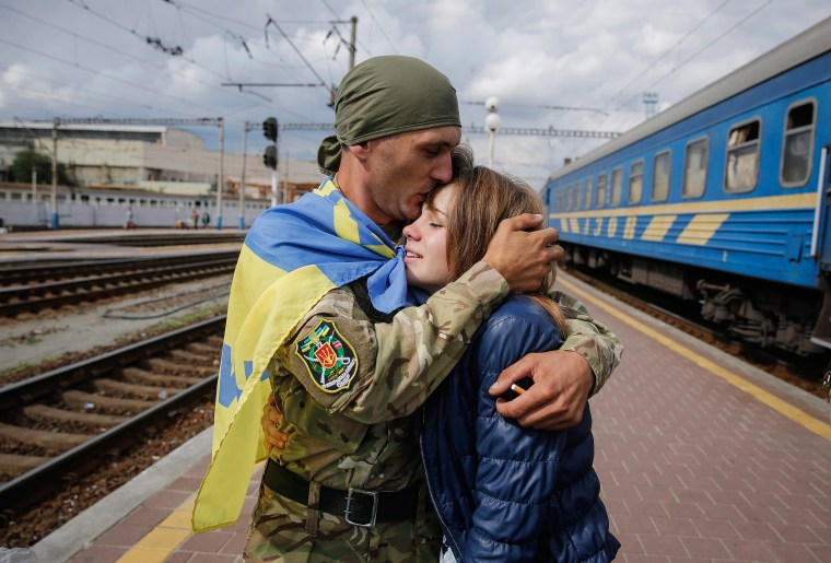 Image: A discharged Ukrainian serviceman kisses his girlfriend on a platform of Kiev railway station