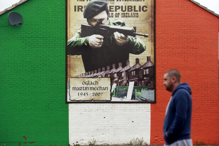 Image: A man walks past a mural supporting the Irish Republican Army