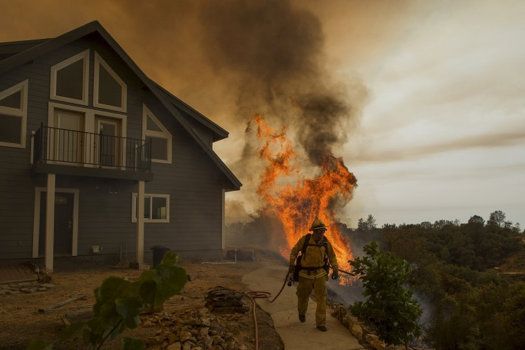 Image: Firefighter works to save a residence as the Butte fire burns in San Andreas, California