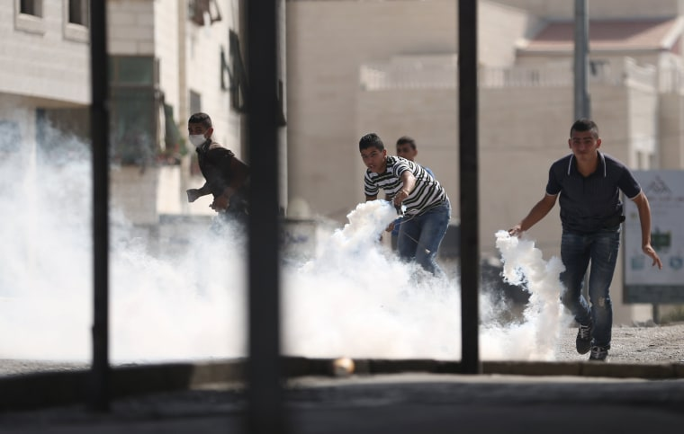 Image: Palestinians prepare to return tear gas canisters fired by Israeli troops during clashes at a protest against an Israeli police raid on Jerusalem's al-Aqsa mosque, in the occupied West Bank town of Al-Ram, near Jerusalem