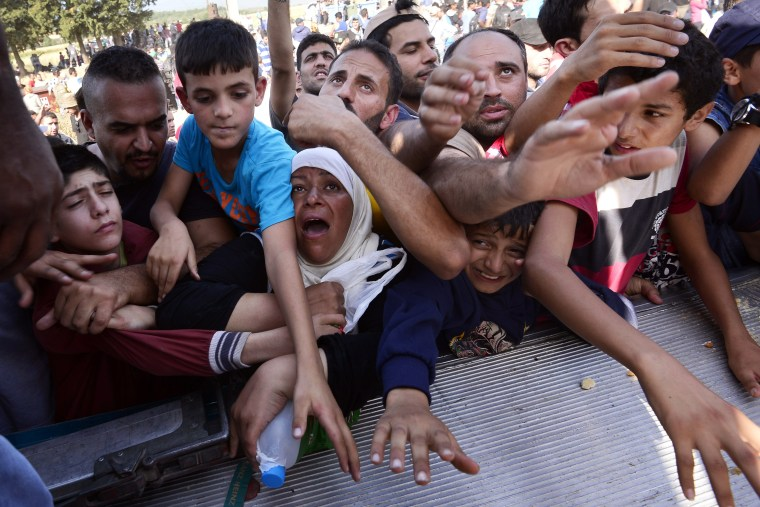 Image: Migrants reach for food in Greece