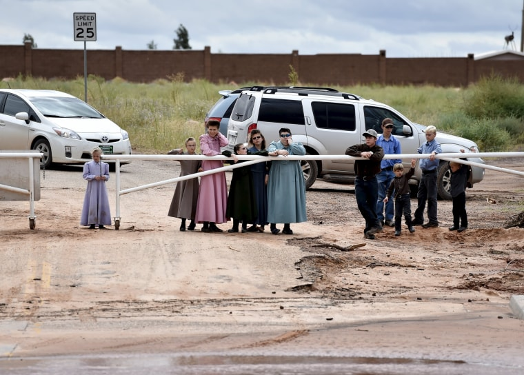 Image: Residents watch rescuers search along the Short Creek after a flash flood in Hildale, Utah