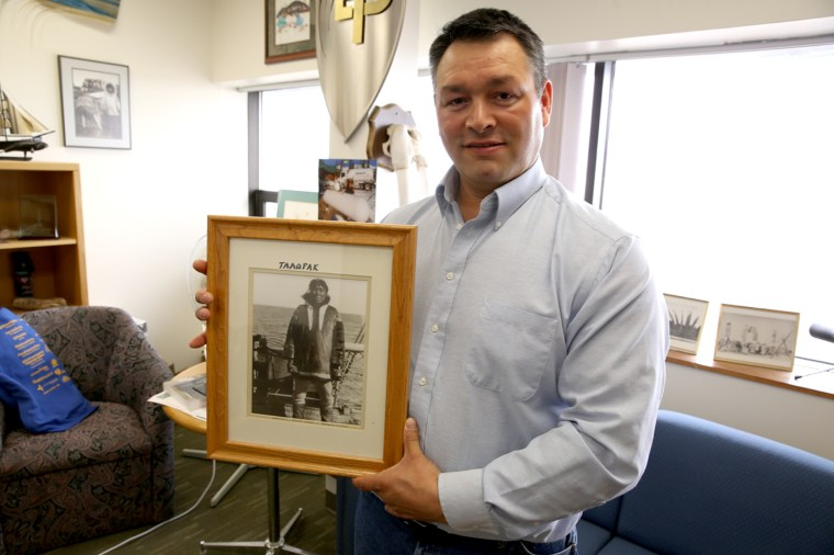Crawford Patkotak holds a photo of his great-grandfather. He and his kids are navigating a changing way of life in Barrow, Alaska.