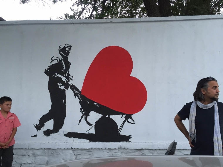Image: Kabir Mokamel paints on a concrete blast wall
