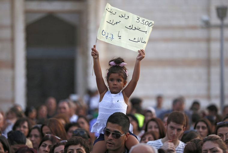 Image: An Israeli Christian child holds a banner during a rally