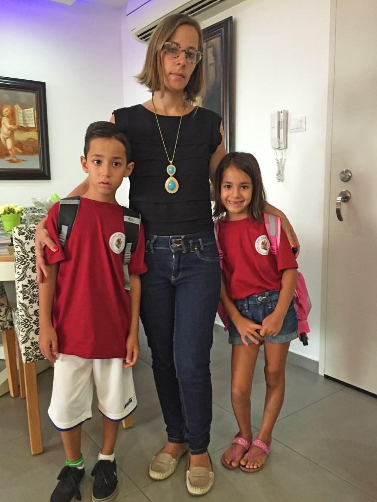 Rula Azar, 35, poses with her children, Joyce Azar, 6, and Jirius, 9, in their home in Ramla, Israel.