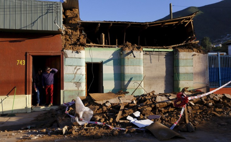 Image: A resident looks on near debris of a damaged house after an earthquake hit areas of central Chile, in Illapel.