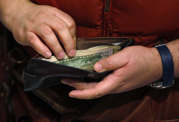 Image: A customer opens his wallet at a Macy's cash register on Black Friday in New York