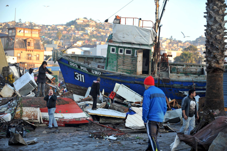Image: People recover items from destroyed houses next to a ship dragged by the waves after a earthquake hit areas of central Chile, in Coquimbo city