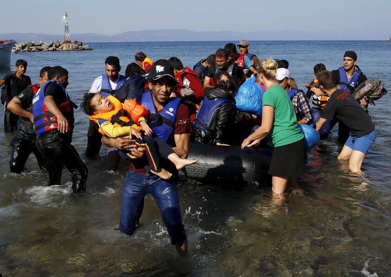 Image: A Syrian refugee carries his child at a beach on the Greek island of Lesbos after crossing part of the Aegean Sea from the Turkish coast