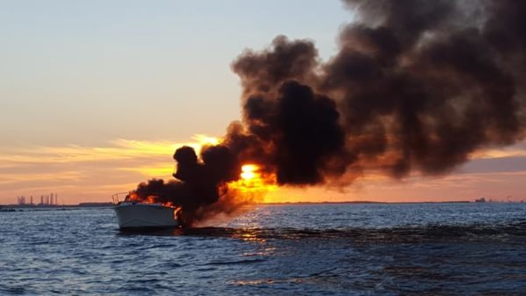 A yacht is seen on fire after four people were rescued by a boater in the waters near Galveston, Texas, on Saturday.