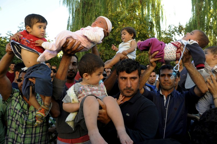 Image: Migrants lift their children during protest in Edirne