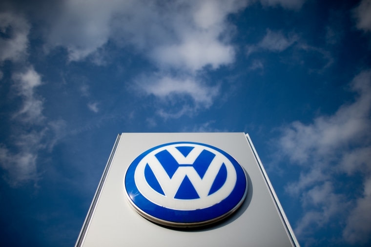 A sign with the Volkswagen logo stands in front of a VW car dealer in Hanover, Germany, in 2014.