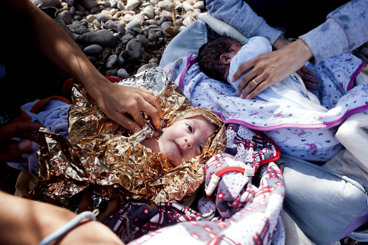 Image: Eight-month old twins from Syria lie on Eftalou beach, west of the port of Mytilene, on the Greek island of Lesbos after their parents crossed the Aegean sea from Turkey
