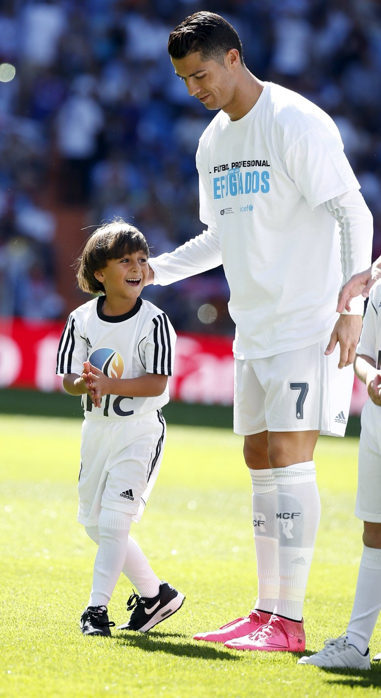 Image: Zaid, 7, son of Usama Abdul Mohsen, a Syrian refugee who was filmed being tripped by a camerawoman as he fled police in Hungary with him stands next to Real Madrid's Ronaldo before the Spanish first division soccer match in Madrid