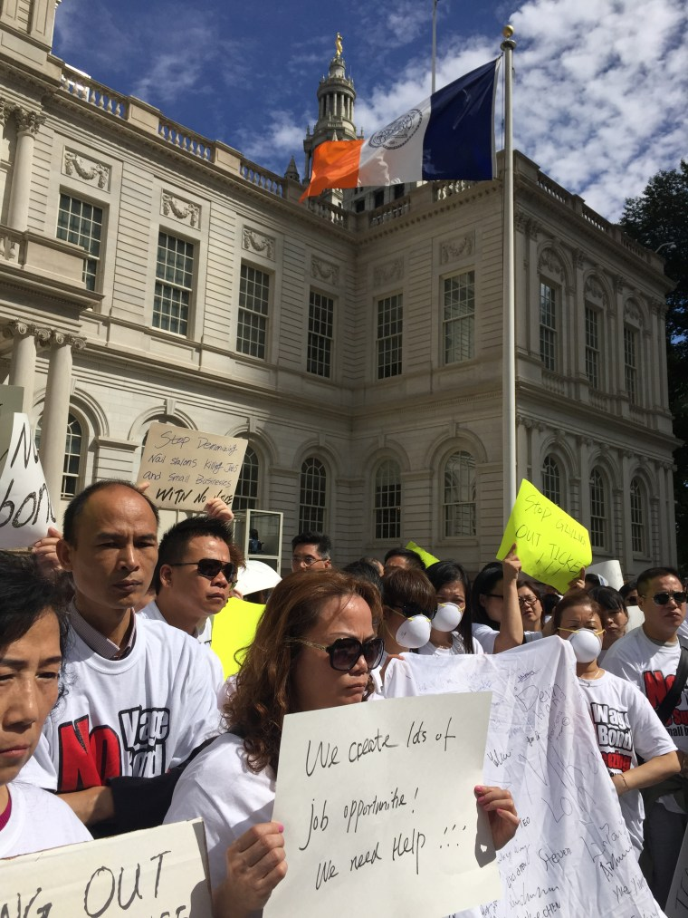 Demonstrators hold up signs protesting provisions of New York State's nail salon law, including a requirement that salon owners with two-or-more full-time employees purchase wage bonds before Oct. 6.