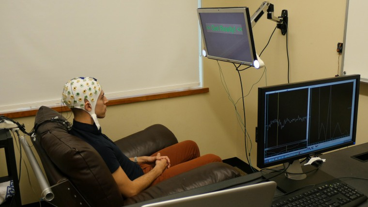 """University of Washington graduate student Jose Ceballos, the experiment's """"respondent,"""" wears a cap connected to an electroencephalography (EEG) machine that records brain activity and sends a response to a second participant, the """"inquirer,"""" over the Internet."""