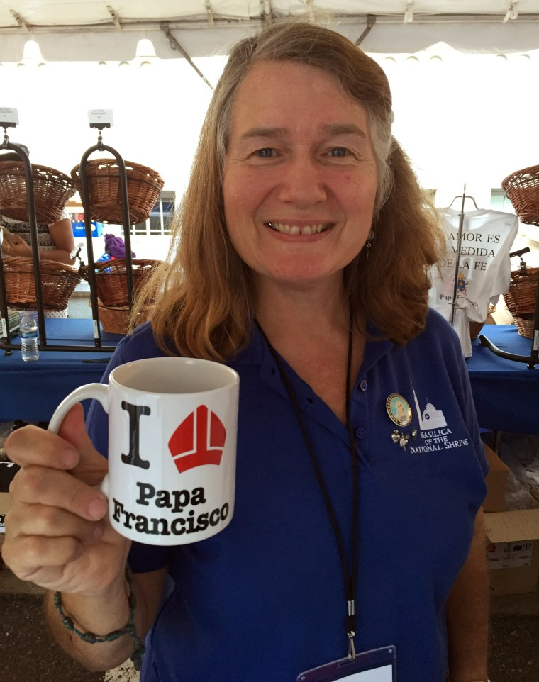 Cathy Bewley, staffing the gift shop at the Basilica of the National Shrine, holds up a $10 mug. There are now long lines to check out the merch.
