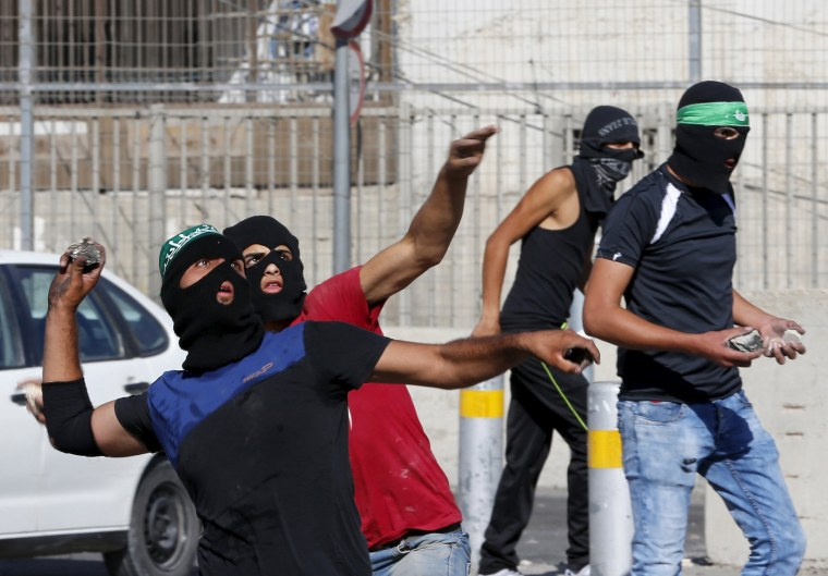 Image: Palestinians hurl stones towards Israeli border police