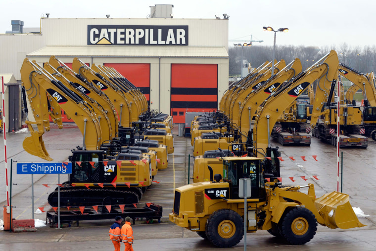 Image: Workers walk past Caterpillar excavator machines at a factory in Gosselies