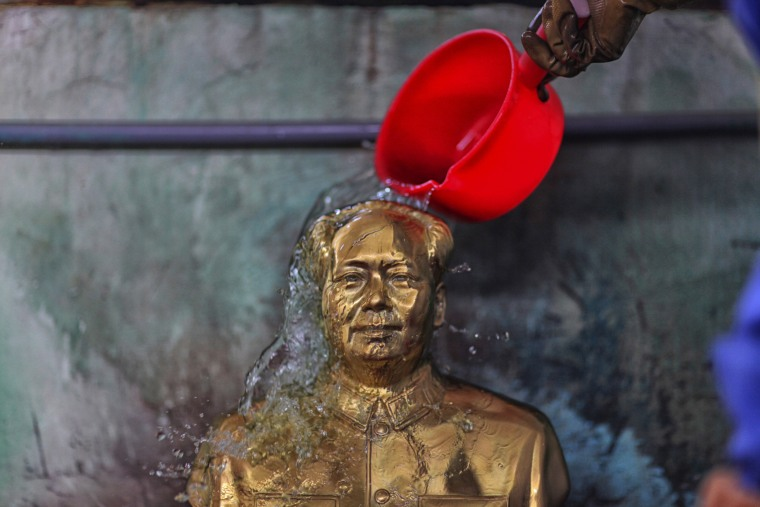 A worker pours water onto a statue of Mao Zedong in 2013 at a factory in Shaoshan, Mao's hometown.