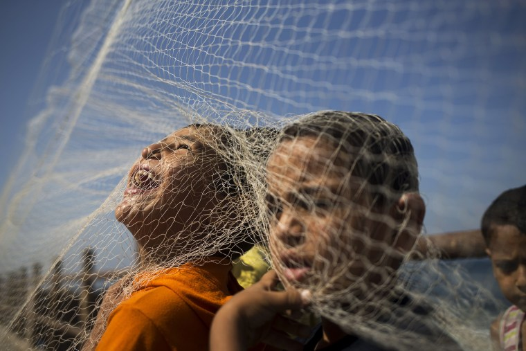 Image: Palestinian boys play with a fish net on the beach in Gaza City