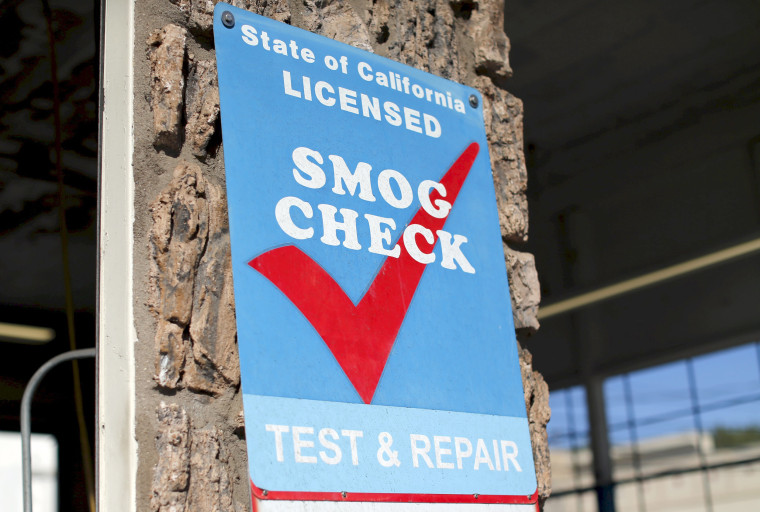 Image: A smog testing facility sign is shown marking a garage as a certified testing station for vehicles in Encinitas, California