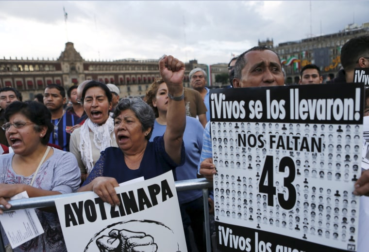 Image: Demonstrators hold placards as relatives (not pictured) of some of the 43 missing students of Ayotzinapa College Raul Isidro Burgos attend a news conference after a private meeting with Mexico's President Enrique Pena Nieto in Mexico City