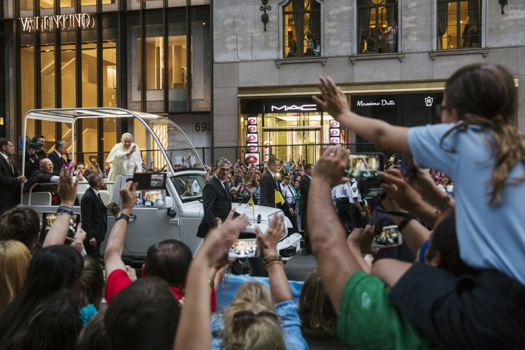 Image: Pope Francis waves from his vehicle as he is driven down 5th avenue