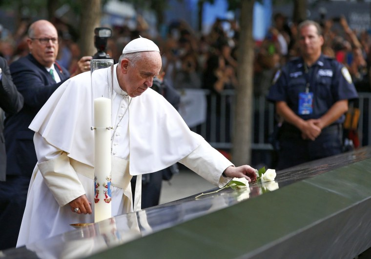 Image: Pope Francis places a flower after praying for the victims at the September 11, 2001 memorial in New York