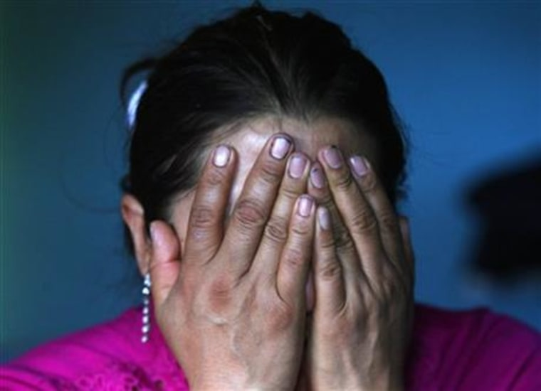 In this Aug. 8, 2015 photo, Afrodita Mondragon, mother of slain student Julio Cesar Mondragon, covers her face in grief as she speaks inside her home in San Miguel Tecomatlan, a rural town in the hills of Mexico state. Unlike the families of the 43 students who disappeared a year ago, Julio's loved ones were left with a body to bury. But there is little comfort in that, because his corpse bore witness to the horror of his final moments. His autopsy showed several skull fractures and other injuries and internal bleeding to his body consistent with torture. His face had been flayed, a tactic often used by the drug cartels to incite terror and send a message.