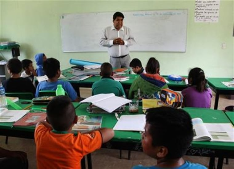 In this Sept. 15, 2015 photo, Cuitlahuac Mondragon, the uncle of slain college student Julio Cesar Mondragon, teaches at an elementary school in San Miguel Tecomatlan, a rural town in the hills of Mexico state. Julio was slain on Sept. 26, 2014 in Iguala during an attack in which 43 students disappeared. Julio liked to challenge the teachers, Cuitlahuac said. He also taught reading and writing to poor families in San Miguel Tecomatlan, a rural town in the hills of Mexico state.