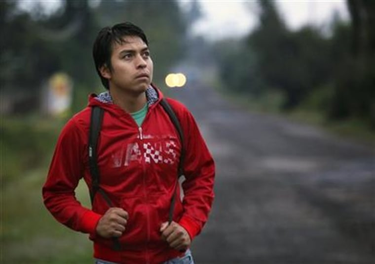 """In this Sept. 15, 2015 photo, Lenin Mondragon, the brother of slain college student Julio Cesar Mondragon, walks in San Miguel Tecomatlan, a rural town in the hills of Mexico state. Lenin's brother was killed one year ago on Sept. 26, 2014 in Iguala during an attack that left 43 students disappeared. The family gathers most Saturdays at the large table in their uncle Cuitlahuac's modest concrete home, sometimes to meet with their lawyer, sometimes for psychological counseling, and always to plot a path to justice. """"Here we all pretend to be strong,"""" said Lenin, who has his brother's eyes, now always filled with sadness."""