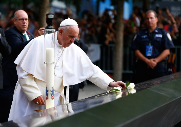 Image: Pope Francis places a flower after praying for the victims at the September 11, 2001 memorial