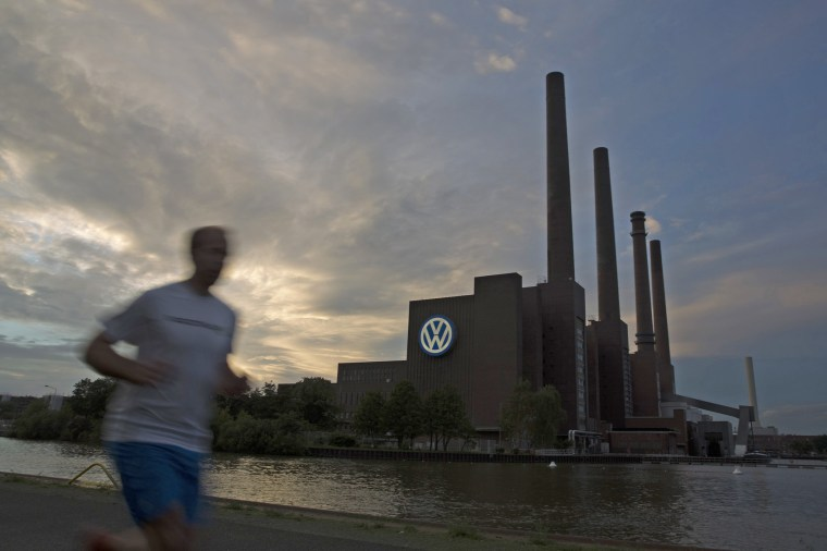 Image: Jogger runs along bank of Midland Canal in front of Volkswagen power plant in Wolfsburg
