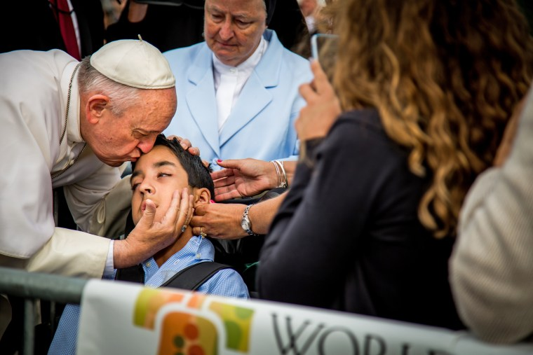 Pope Francis kisses Michael Keating, a 10-year-old boy who suffers from cerebral palsy, after arriving in Philadelphia.