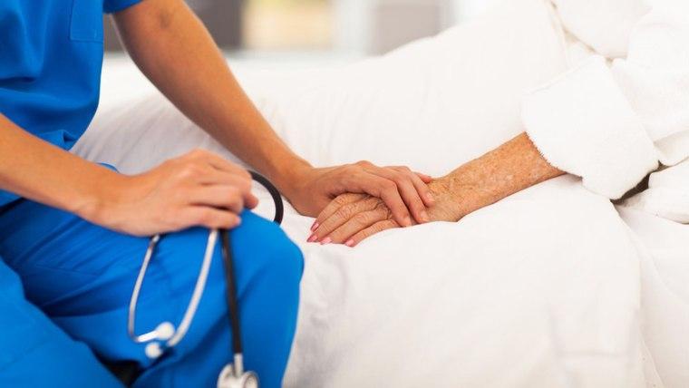 Nurse holds elderly patient's hand