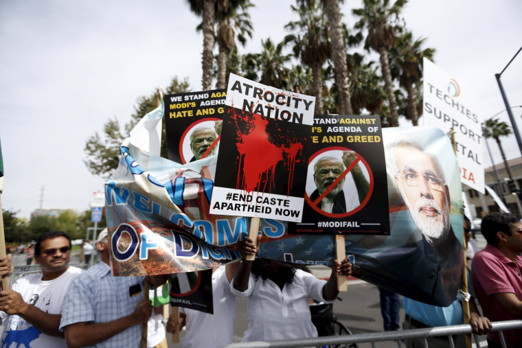Image: Demonstrators hold signs in protest against Indian Prime Minister Narendra Modi before a community reception in San Jose, California
