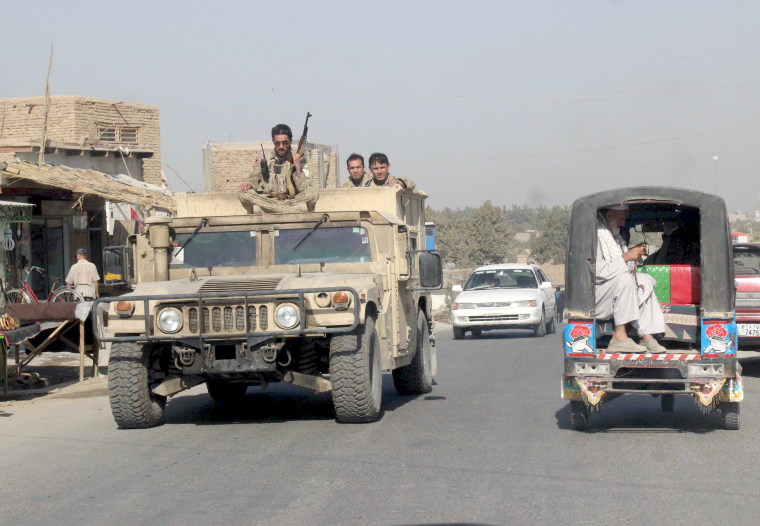 Image: Afghan security forces travel on an armored vehicle in Kunduz province