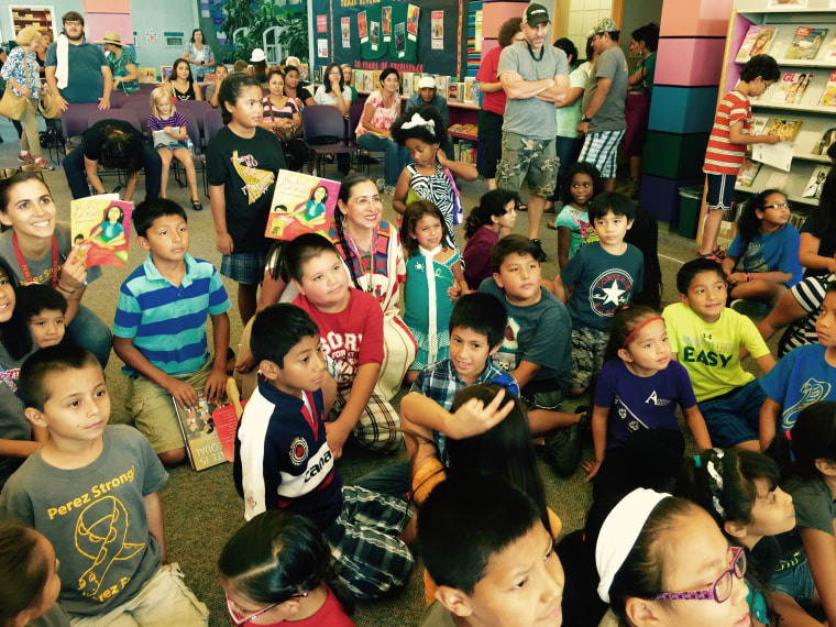 Author Amada Irma Perez poses with children and parents following her reading at the 2015 Tomás Rivera Award Literature Fair in San Marcos, Texas.