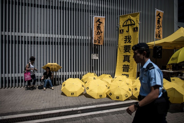 Image: A police officer walks past yellow umbrellas on the anniversary of Occupy Central